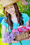 Beautiful woman in a straw hat with basket of flowers Royalty Free Stock Photos