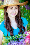 Beautiful woman in straw hat with a bouquet of flowers Royalty Free Stock Photography