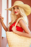 Beautiful woman in straw hat with large brim. Beautiful blonde with long,thick,curly hair and gray-green eyes,beautiful makeup and red lipstick,a yellow straw royalty free stock images
