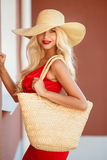 Beautiful woman in straw hat with large brim. Beautiful blonde with long,thick,curly hair and gray-green eyes,beautiful makeup and red lipstick,a yellow straw stock photography