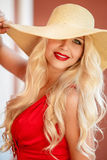 Beautiful woman in straw hat with large brim. Beautiful blonde with long,thick,curly hair and gray-green eyes,beautiful makeup and red lipstick,a yellow straw stock photo