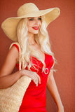 Beautiful woman in straw hat with large brim. Beautiful blonde with long,thick,curly hair and gray-green eyes,beautiful makeup and red lipstick,a yellow straw stock image
