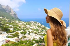 Beautiful woman with straw hat looking at Capri sight from terrace, Capri Island, Italy Stock Photos