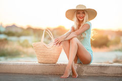 Beautiful woman in a straw hat at sunset. A slender woman,with long blond hair in straw hat with large brim,blue shorts and blue t-shirt,standing next to the bag Stock Image