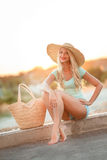 Beautiful woman in a straw hat at sunset. A slender woman,with long blond hair in straw hat with large brim,blue shorts and blue t-shirt,standing next to the bag Royalty Free Stock Photo