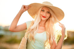 Beautiful woman in a straw hat at sunset. A slender woman,with long blonde hair in a straw hat with large brim,blue shorts and blue t-shirt,on the shoulder woven Royalty Free Stock Image