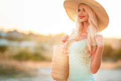 Beautiful woman in a straw hat at sunset Stock Photo