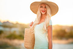 Beautiful woman in a straw hat at sunset. A slender woman,with long blonde hair in a straw hat with large brim,blue shorts and blue t-shirt,on the shoulder woven Stock Image
