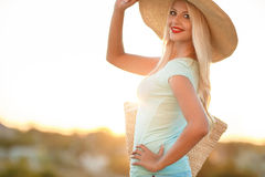 Beautiful woman in a straw hat at sunset. A slender woman,with long blonde hair in a straw hat with large brim,blue shorts and blue t-shirt,on the shoulder woven royalty free stock photo