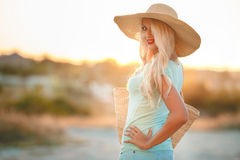 Beautiful woman in a straw hat at sunset. A slender woman,with long blonde hair in a straw hat with large brim,blue shorts and blue t-shirt,on the shoulder woven Stock Photography