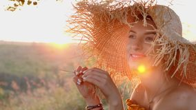 Beautiful woman in straw hat. The young and beautiful women in nature.Beautiful woman in straw hat. Closeup. Slow motion. Sunset at background stock footage