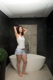 Beautiful woman stretching in bathroom. Royalty Free Stock Image