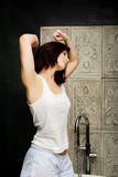 Beautiful woman stretching in bathroom. Stock Photography