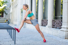 A beautiful woman stretching her leg against pipes Royalty Free Stock Photography
