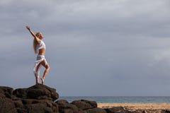 Beautiful woman stretching on lava rocks Stock Photography
