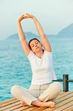 Beautiful woman stretching in the morning while sitting on a pier at the sea Royalty Free Stock Photo