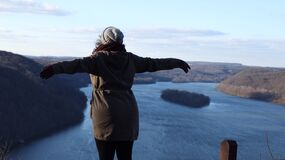 Beautiful woman stretching out her arms while looking out towards a breathtaking view of the Susquehanna  a