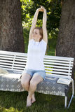 Beautiful woman stretching out. A beautiful woman stretching out on a white bench in a park on a sunny day Stock Images