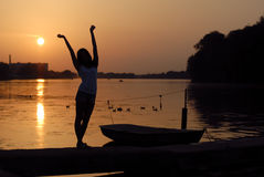 Beautiful woman stretching on river bank at sunset Royalty Free Stock Photography