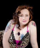 Beautiful woman striking golden eyes and tattoos. Beautiful woman with auburn hair and striking gold eyes wearing leopard print with tattoos royalty free stock photography