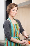 Beautiful woman in striped apron cooks vegetables Royalty Free Stock Photography