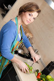 Beautiful woman in striped apron cuts vegetables Stock Photography