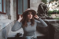 Beautiful woman in a striped shirt and hat. Holds the camera near the statue of a lion against the background of the old royalty free stock photography