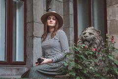Beautiful woman in a striped shirt and hat. Holds the camera near the statue of a lion against the background of the old stock photo