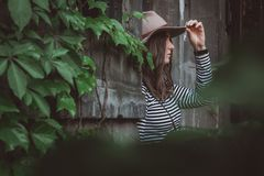 Beautiful woman in a striped shirt holding her hat. royalty free stock image