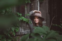 Beautiful woman in a striped shirt holding her hat and looking at a camera. stock photo