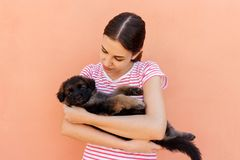 Beautiful woman in striped T-chirt holding small dog.  Royalty Free Stock Images