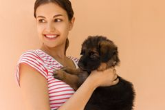 Beautiful woman in a striped T-shirt smiles and holds a small puppy.  Royalty Free Stock Images