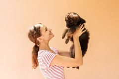 Beautiful woman in a striped T-shirt smiles and holds a small puppy.  Stock Image