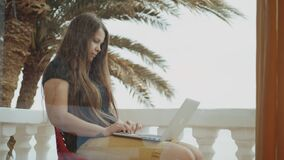 Beautiful woman student or freelancer working on a laptop, woman sitting in balcony with top view palm and sea, rapid