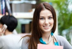 Beautiful woman student at the library against bookshelves Stock Photos