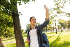 Beautiful woman student walking in park holding laptop. Image of happy young beautiful woman student walking in park holding laptop waving royalty free stock photography