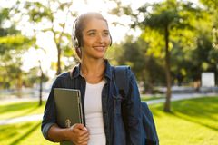 Beautiful woman student walking in park holding laptop listening music. Image of happy young beautiful woman student walking in park holding laptop listening royalty free stock photos