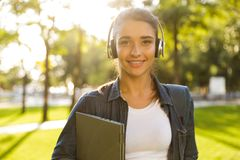 Beautiful woman student walking in park holding laptop listening music. Image of happy young beautiful woman student walking in park holding laptop listening stock images