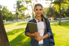 Beautiful woman student walking in park holding laptop looking camera. Image of happy young beautiful woman student walking in park holding laptop looking stock image