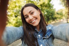 Beautiful woman student walking in the park take a selfie by camera. stock photo