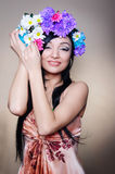 Beautiful woman in the studio with a wreath of flowers on her he Stock Photo