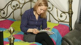 Beautiful woman studying on a bed in her room with laptop. on-line education.  stock video
