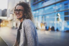Beautiful woman in stylish clothing wearing eye glasses outside in the european night city. Bokeh and flares effect on. Blurred background royalty free stock photo