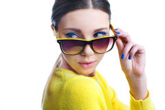 Beautiful woman with stylish colorful make up in sunglasses. Stylish beautiful woman in sunglasses and yellow sweater with creative colorful make up and blue Royalty Free Stock Photo