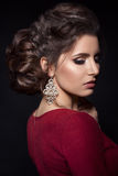 Beautiful woman with stylish haircut and big earrings looking down over shoulder, touching neck by hand. Brunette girl posing in d Stock Image