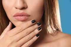 Beautiful woman with stylish nail polish on color background royalty free stock photos