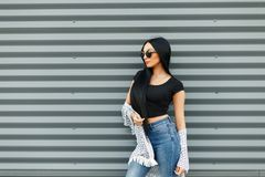 Beautiful woman in a stylish summer look clothes with fashion. Sunglasses near the metal wall stock photo