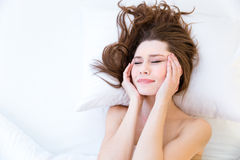Beautiful woman suffering from headache on bed Royalty Free Stock Photos