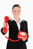 Beautiful woman in suit holding a red telephone Stock Photography
