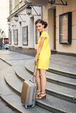 Beautiful woman with the suitcase at the entrance to the hotel Stock Photography